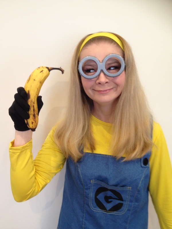 Lady dressed as a minion with minion at goggles on holding a banana for a minion party at Spellbound Parties