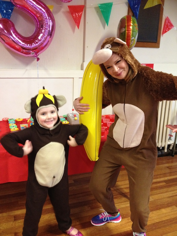 Small child in a monkey suit with women in Curious George monkey suit and inflatable banana at Spellbound Parties