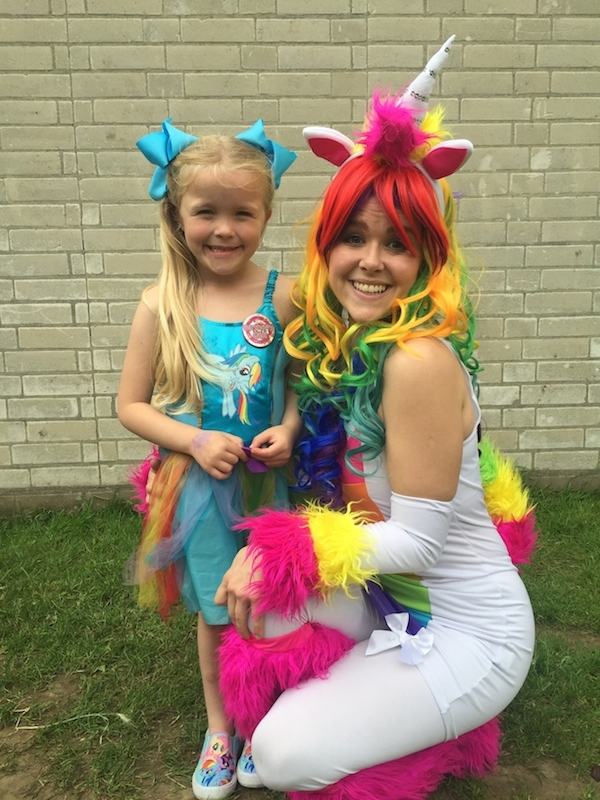 Lady dressed as rainbow unicorn with little girl in a My Little Pony dress